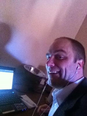 Quincy Larson wearing a suit and headphones, sitting with his netbook at his kitchen table.